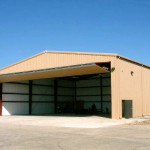 Sagebrush Tan steel airplane hangar with open garage door