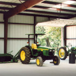 Inside steel farm shop with tractors and red steel framing