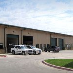 Steel building office and shop combination with green garage doors