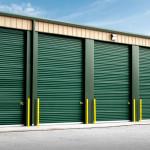 Steel storage units with green garage doors
