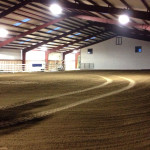 Interior of indoor riding arena with steel framing and dirt floor