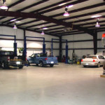 Inside automotive shop with steel framing and cars