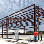 Warehouse under construction with red steel framing