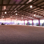 Interior of covered riding arena with dirt floor