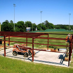 Steel batting cage under construction with red steel framing