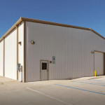 White commercial steel building with parking lot