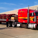 Truck delivering red steel framing for building construction