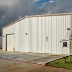 Steel workshop building with parking lot