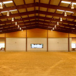 Indoor steel agricultural building with dirt floor and windows