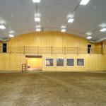 Indoor steel horseback riding arena with wooden wall