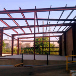 Lean to add on building with red steel framing
