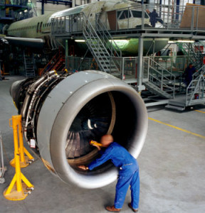man works on jet engine in a steel aircraft hangar