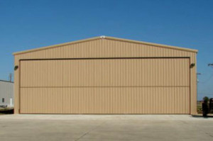 tan steel aircraft hangar with bi-fold door