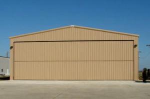 tan steel aircraft hangar with bi-fold door