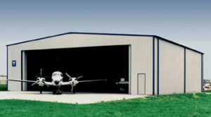 private plane sitting outside a gray steel aircraft hangar with blue trim