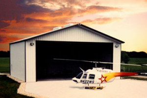 helicopter sitting outside a steel aircraft hangar