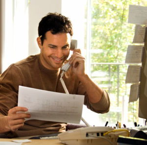 Photo of a smiling man on a phone with a customer service rep.
