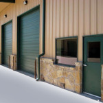 Green and tan steel automotive shop with stone accents