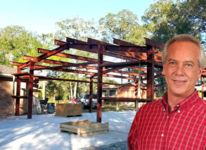 Happy man stands in front of his roomy steel workshop going up.