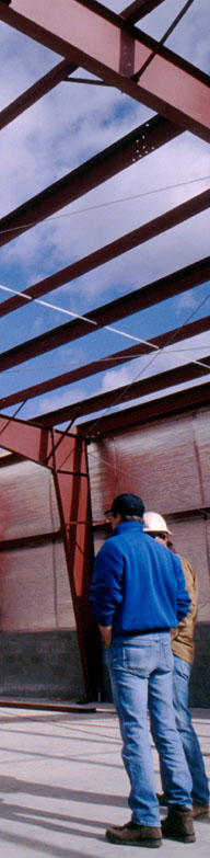 Commercial steel building framers inside a pre-engineered metal building under construction