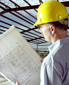 Image of a man in a hard hat reading plans with steel framing in the background.