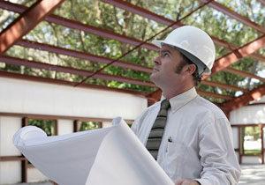 Builder in hard hat examines steel building system.