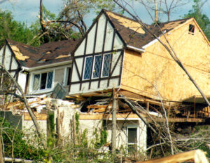 Photo of a badly damage wood house after a severe storm.