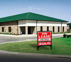 Photo of a RHINO commercial steel building with brick exterior and a green metal hip roof.