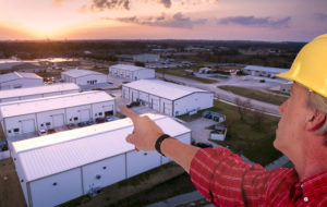 A builder points to a business park of commercial steel buildings.