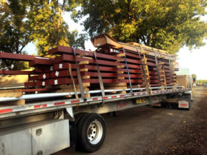 Photo of a steel prefab building kit shipping on a truck.