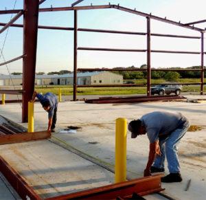 Photo of two men assembling a RHINO building.