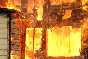 Photo of a flammable wood building on fire.