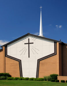Photo of a steeple-topped steel church with brick trim.