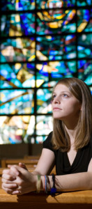 Woman prays in front of a steel glass window in this discussion of steel church buildings