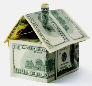 Photo of hundred dollar bills folded to form a small house.