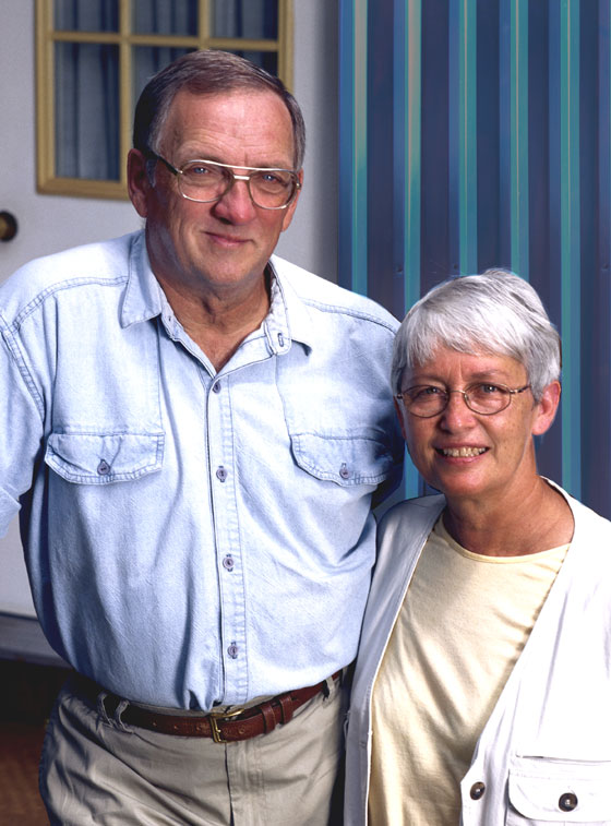 Older couple stands before their metal building guest house