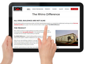 Hands holding a digital tablet with The RHINO Difference web page on the screen.