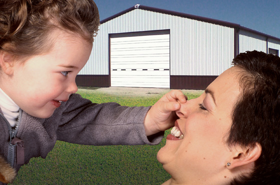 Mother plays with toddler before a white steel building with brown trim