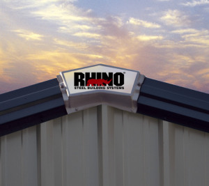 Close up of a RHINO Steel Buildings sign on the peak of a metal building roof