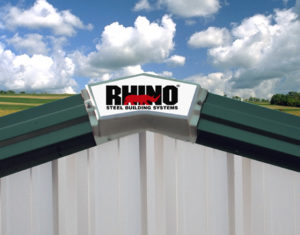 Image shows the RHINO logo on the roof peak of a steel building.
