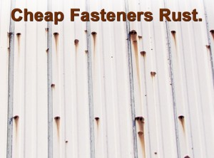 Closeup of a steel building side panel with streaks of rust caused by cheaply made screws
