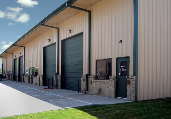 An attractive tan and green industrial metal building with large bay doors and rock trim