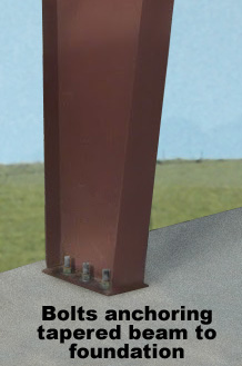 Closeup of a steel building column bolted to a foundation