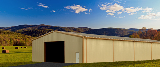 Long agricultural metal building with gold trim against a background of rolling, tree-covered hills and hay pastures