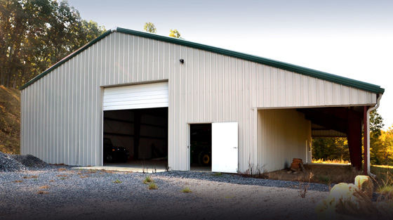 White agricultural metal building with dark green trim