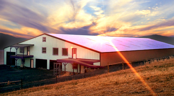 Huge steel barn with a red metal roof at sunset