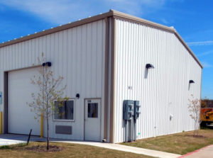 Photo of a white RHINO metal building with tan trim and gutters.
