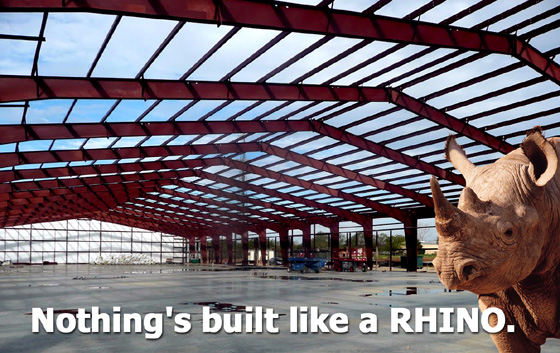 """A rhino stands in a massive clear-span steel warehouse under construction, with the heading: """"Nothing's Built Like a RHINO."""""""