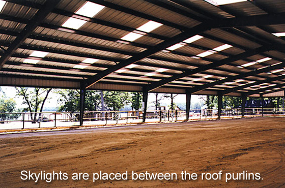 The skylighted roof of  steel riding arena