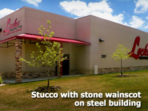 RHINO steel building finished in tan stucco with tan-and-brown stone trim